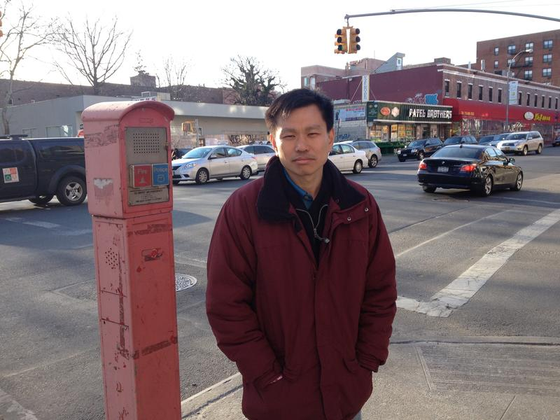 Hsi-Pei Liao at an intersection in Flushing. Behind him is the street where his four-year-old daughter, Allison, was struck and killed by an SUV.