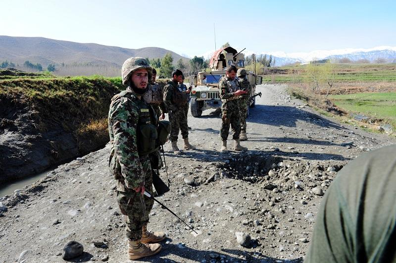 On 3/18/14 an Afghan soldier (L) attached to the 4th Brigade, 201 Army Corps of the Afghan National Army (ANA) stands next to a crater after an IED was triggered by insurgents using a mobile phone.