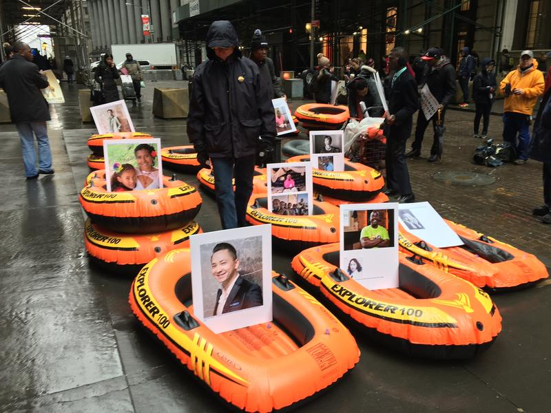 Activists set up inflatable rafts holding the pictures and stories of refugees in front of the Trump Building on Wall Street, as part of a day of action to draw attention to their plight.