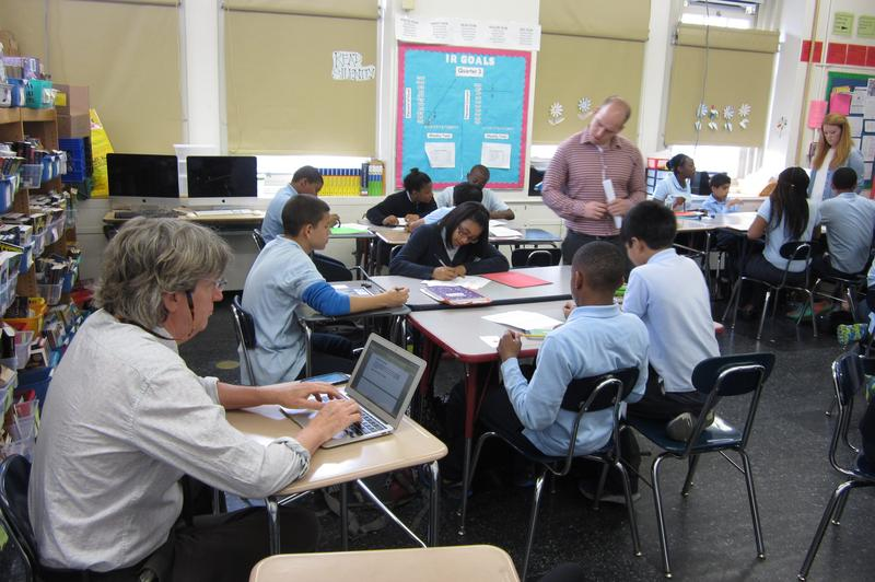 Principal John Curry observing teacher Noah Foster at work, at the Community Action Middle School
