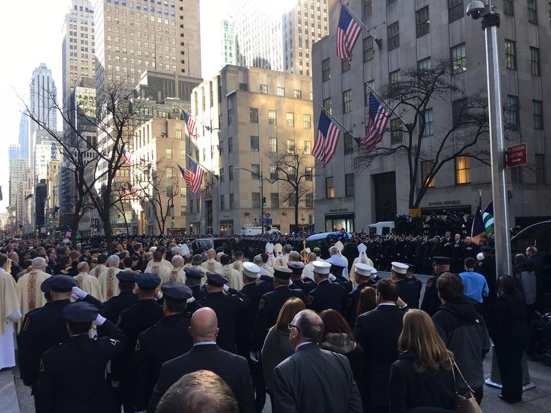 Thousands of mourners look on as Detective Steven McDonald's casket emerges from St. Patrick's Cathedral.