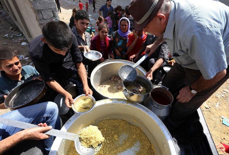 Iraqi Yazidi families who fled the violence in the northern Iraqi town of Sinjar, are given food at a school where they are taking shelter in the Kurdish city of Dohuk