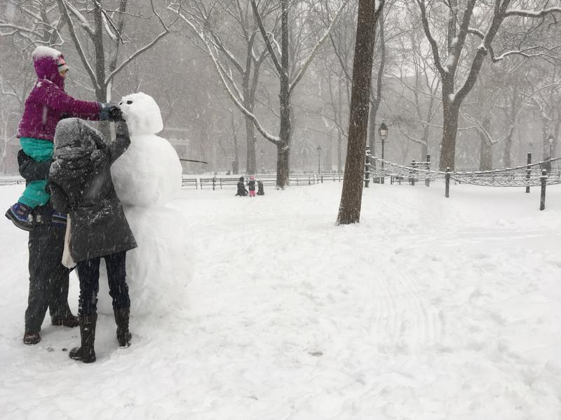 Chris Robertson and his daughter Sofia put the finishing touches on  a snowman in Washington Square Park, on February 9, 2017. (Shumita Basu/WNYC)