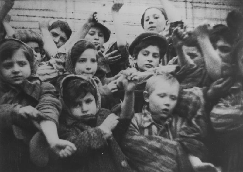 Michael Bornstein (bottom right, at age 4) and other children show their number tattoos to Soviet soldiers at Auschwitz in the days after liberation.