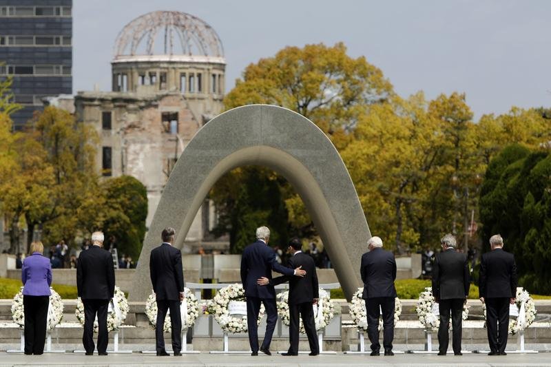 US Secretary of State John Kerry (center L) puts his arm around Japan's Foreign Minister Fumio Kishida (center R) at the memorial site in Hiroshima.