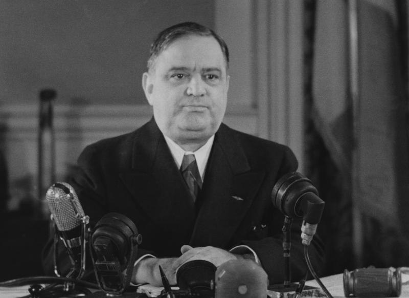Caption:Mayor of New York City Fiorello La Guardia, surrounded by microphones, circa 1940.