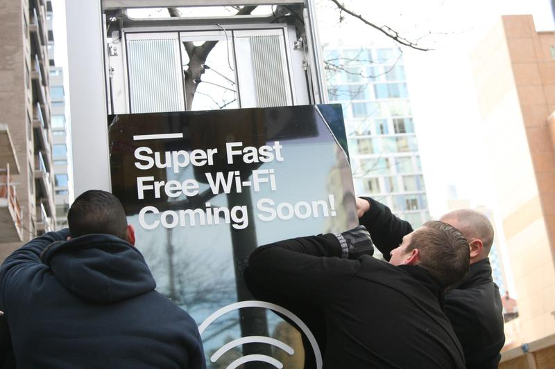 Workers install the first LinkNYC free Wi-Fi kiosk at Third Avenue and 15th Street