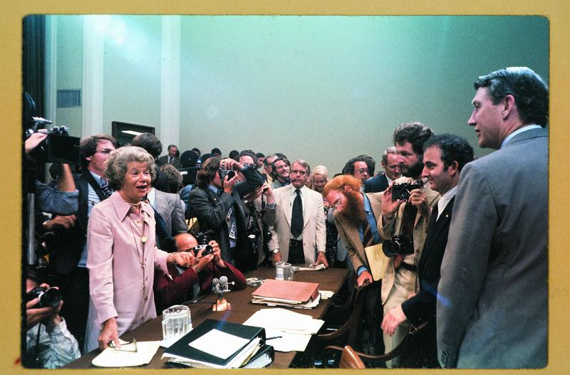 Mary McGrory standing on the left at the Watergate Hearings.