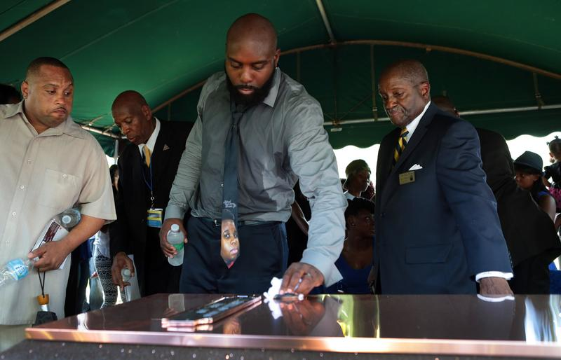 Michael Brown Sr. wipes the top of the vault during the funeral for his son Michael Brown at St. Peters Cemetery on August 25, 2014 in St. Louis Missouri.