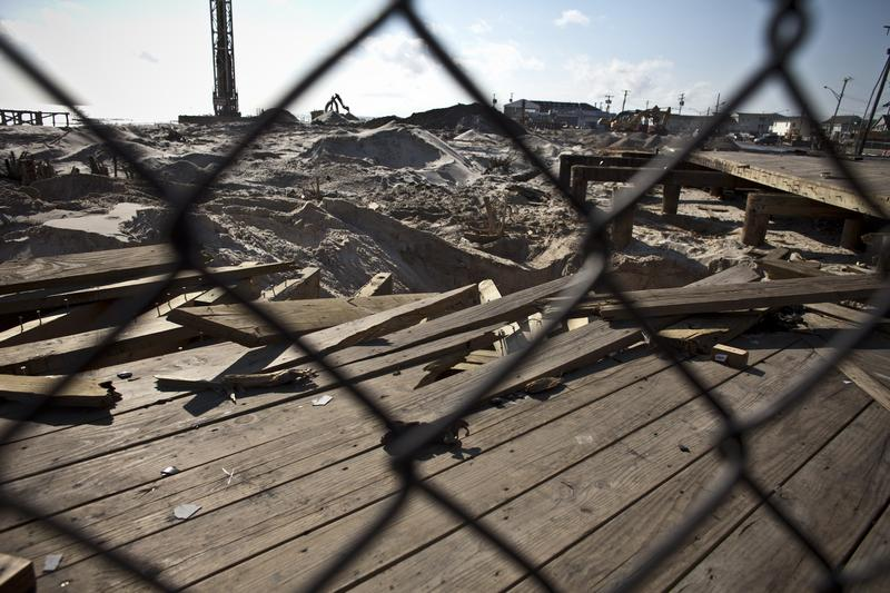 Wood planks damaged by Sandy sit behind a fence in Seaside Heights