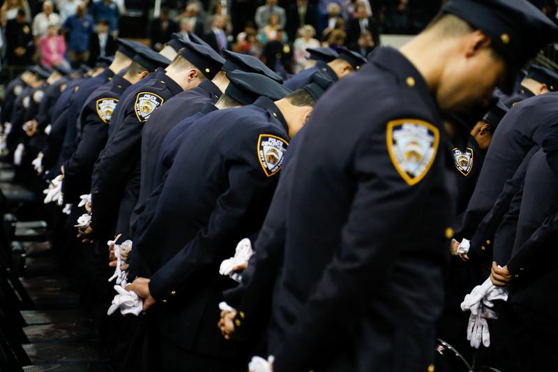 Graduation for 822 new NYPD officers in July 2015. Officer bowed heads in honor of officers who died this past year.