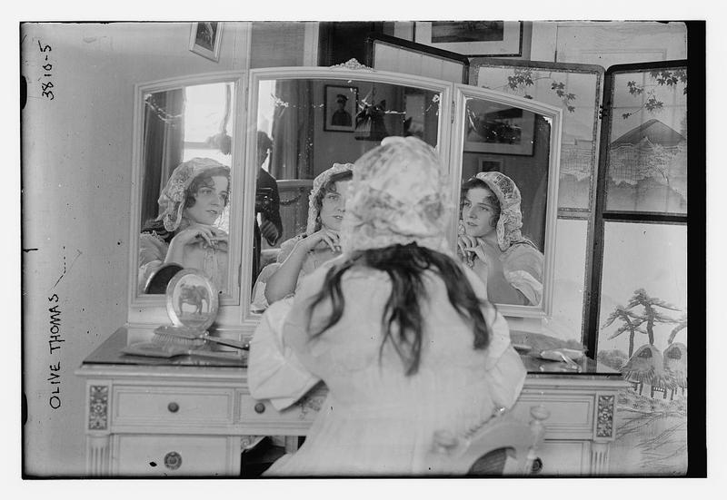 Olive Thomas in April 1916 looking into a mirror with a glimpse of the photographer