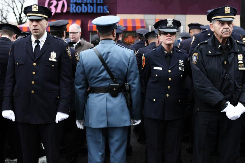 Many police officers turn their back while Mayor Bill de Blasio speaks at the funeral of NYPD officers Wenjian Liu. This, despite pleas from the police commissioner not to protest at funerals.