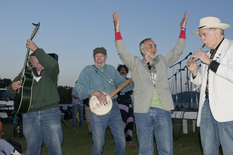 (L-R) unknown guitarist, Pete Seeger (banjo), Raffi Cavoukian, David Amram (tin whistle) play in front of the Hudson River at the Clearwater Festival in Croton Point Park in Croton-on Hudson, N.Y.