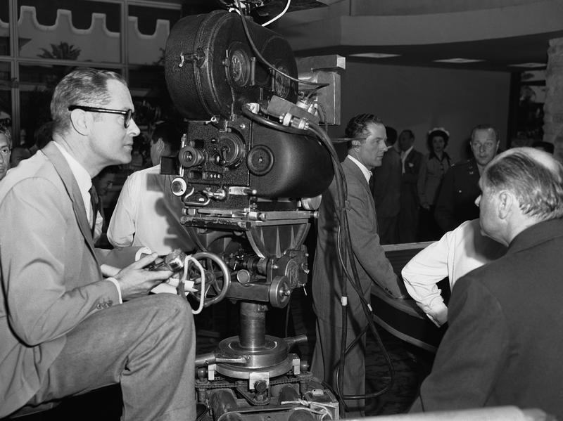 "Actor Robert Montgomery, behind the camera as a scene is prepared, watches his stand-in Robert Spencer playing the part Bob will do during the ""Takes"" , April 24, 1949."