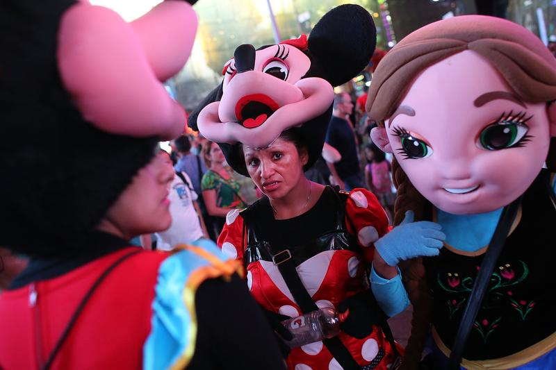 Street performers in costumes take a break in Times Square on August 19, 2015 in New York City.