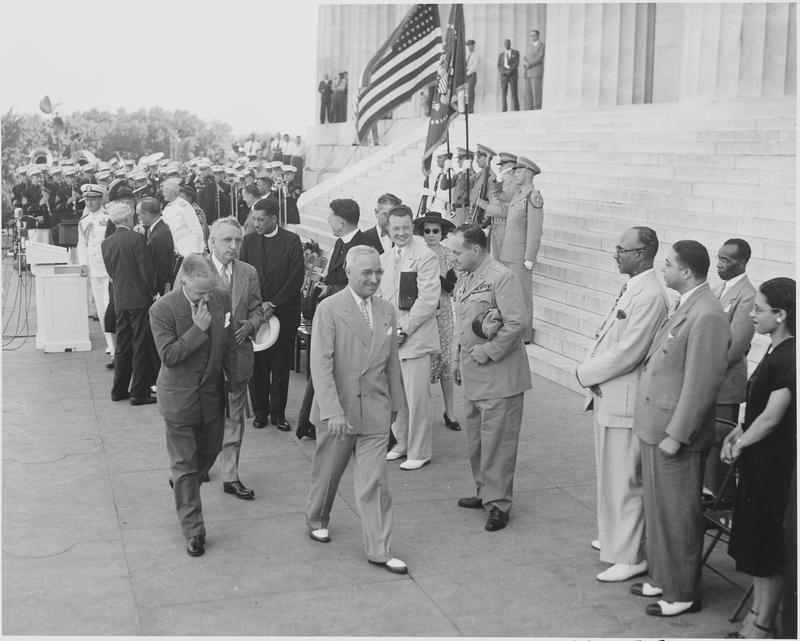President Truman is leaving the podium area, accompanied by Walter White, President of the NAACP (to Mr. Truman's left) and Fred Vinson (between them). Gen. Harry Vaughan is to the right of Truman.