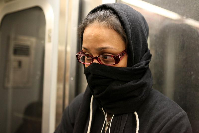 A woman on the L train covers her face, fearful after a doctor with Ebola rode the train.