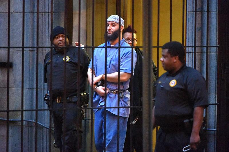 Officials escort 'Serial' podcast subject Adnan Syed from the courthouse following the completion of the first day of hearings for a retrial in Baltimore on Wednesday, Feb. 3, 2016.