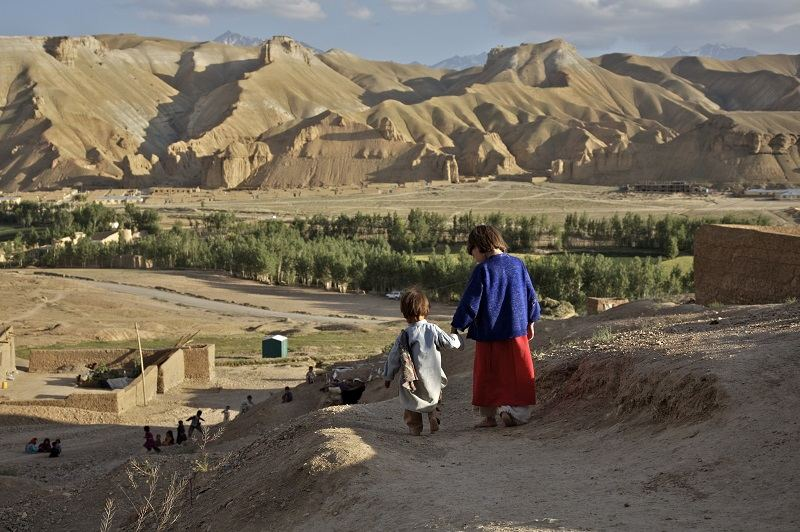 Aqila, 8, leads her 18 month old brother, Abdul Wahid, down the hill, towards other children who are playing in the village of Ragshad, in the central Bamyan Province, Afghanistan, 2007.
