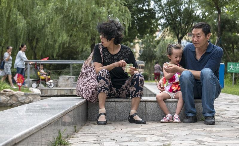 An elderly couple, who left their hometown to live in Beijing, takes care of their only grandchild playing in their residential community,  2015/08/14.