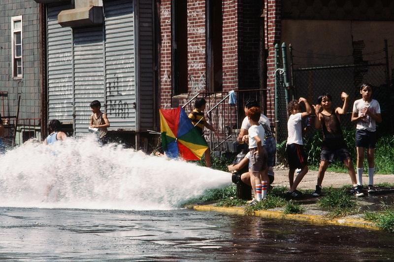 On an unidentified Brooklyn street, a group of children play in the water from an opened fire hydrant in the wake of the New York City blackout, Brooklyn, New York, New York, July 14, 1977.