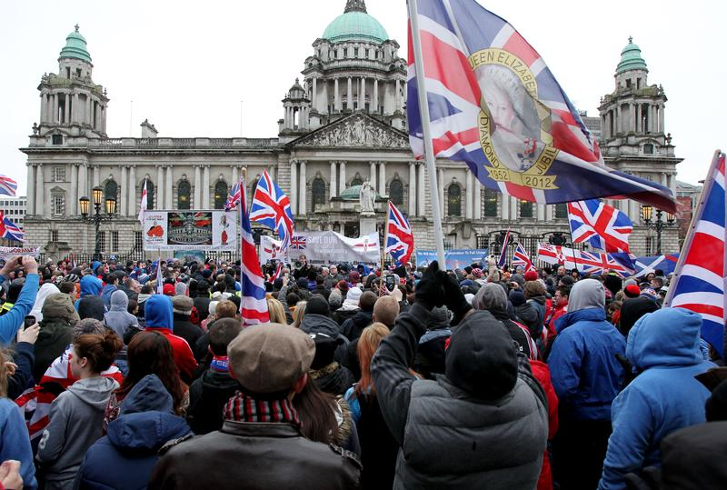 Loyalist protesters hold Union Flags during a demonstration outside Belfast City Hall in Belfast, Northern Ireland on January 19, 2013
