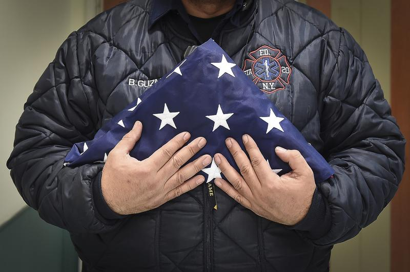 Benny Guzman of FDNY Station 20 in the Bronx holds a flag for a fallen EMT after a fatal incident during an evening shift on Thursday, March 16, 2017 in the Bronx, NY.