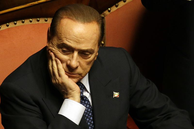People of Freedom party leader Silvio Berlusconi holds up his head at the Senate, in Rome.
