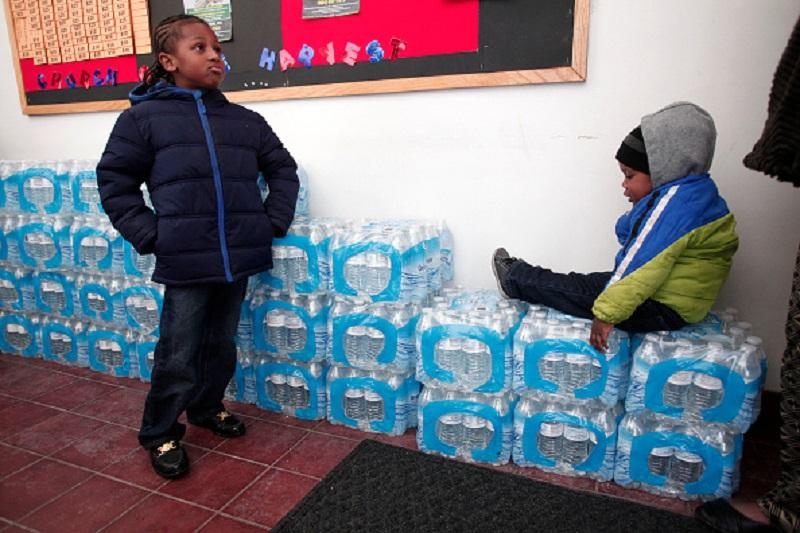 Justin Roberson (L), age 6, of Flint, Michigan and Mychal Adams, age 1, of Flint wait on a stack of bottled water at a rally where the Rev. Jesse Jackson was speaking about about the water crisis.