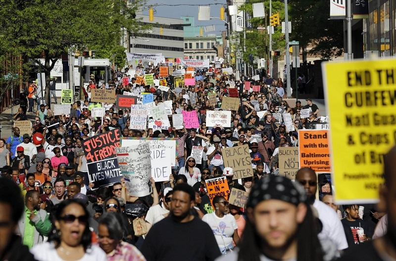 In this May 2, 2015, file photo, protesters march through Baltimore the day after charges were announced against the police officers involved in Freddie Gray's death.