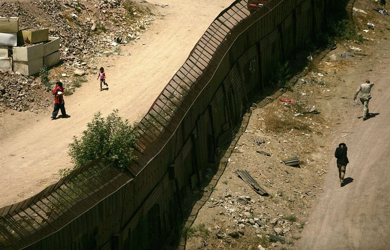 People walk past each other on opposite sides of the fence along the U.S. Mexican border