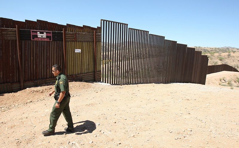 A border patrol agent watches the international border between the U.S. and Sonora, Mexico Friday, April 28, 2006, in Nogales, Ariz.