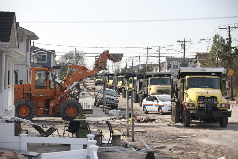 Dump trucks assist with recovery efforts in Breezy Point a week after Sandy hit.