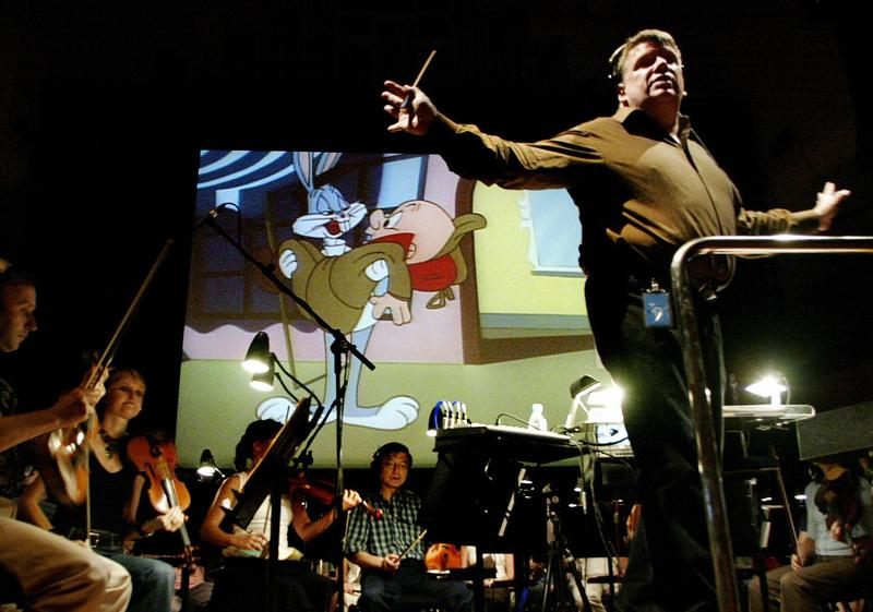 Conductor George Daugherty (R) and members of the Sydney Symphony play as 'Bugs Bunny on Broadway', is projected onto a giant screen during a rehearsal at the Sydney Opera House, February 2005.