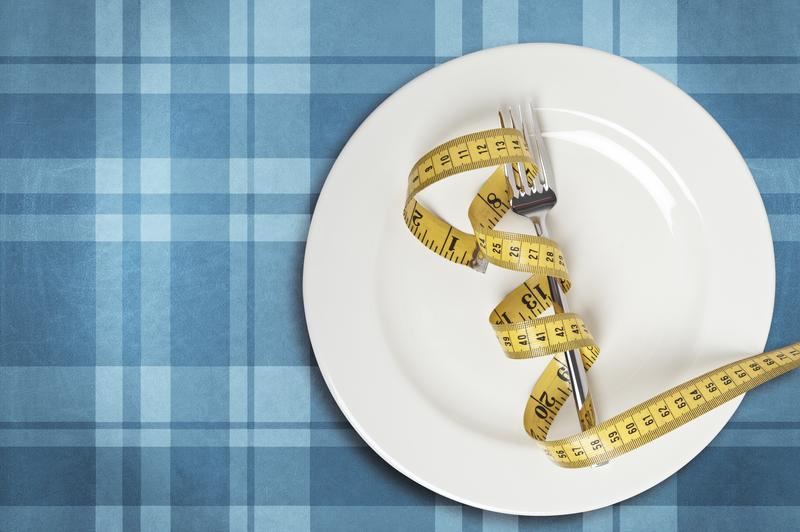 Fork with measuring tape on white plate.
