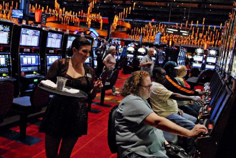 A cocktail waitress takes orders as patrons play slot machines at the Sands Casino Resort Bethlehem in Bethlehem, Pennsylvania, U.S., on Friday, May 22, 2009.