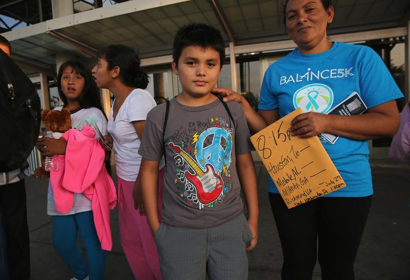 A Salvadorian family waits at the Greyhound bus station for their trip to Houston on July 25, 2014 in McAllen, Texas.