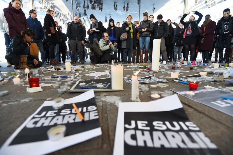 People gather next to signs reading ''I am Charlie'' and candles placed on the ground, after observing a minute of silence in the old Harbor in Marseille on January 8, 2015 for the victims.