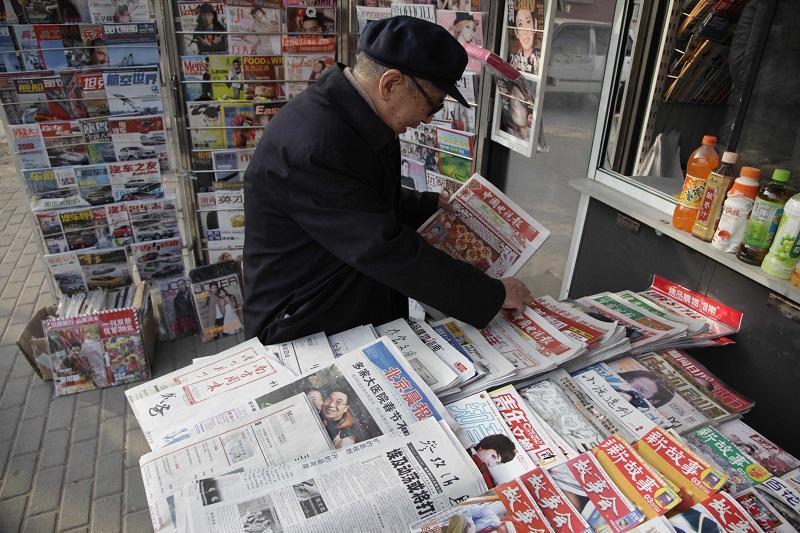 "An elderly Chinese man holds up a newspaper with the front-page of Chinese new year near other one which reads: ""Egypt's disturbances may upset Mideast situation"" at a newsstand in Beijing."