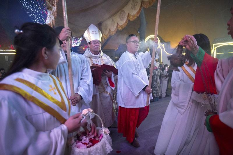 Chinese bishop Joseph Li Shan, center, holds a statue of the baby Jesus as he arrives for a Christmas Eve mass at the Southern Cathedral, Beijing, China, Thursday, Dec. 24, 2015.