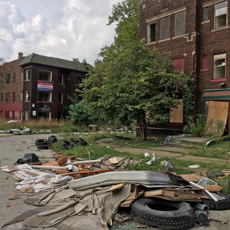 This Aug. 31, 2016, photo shows discarded tires and other refuse piling up on cracked pavement and sidewalks, alongside graffiti-scarred buildings with missing windows in East Cleveland, Ohio.