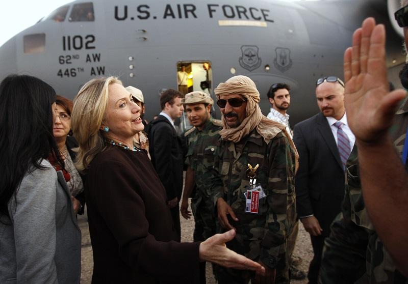 U.S. Secretary of State Hillary Clinton bids farewell to Libyan officials and fighters loyal to the National Transitional Council upon her departure from a one day visit to Tripoli on Oct 18, 2011.
