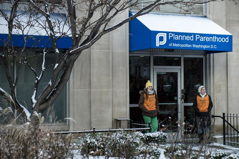 Escorts wait to bring people into a Planned Parenthood before protesters gathered January 24, 2013 in Washington, DC.