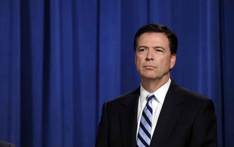 FBI Director James Comey listens during a news conference announcing a deal between the U.S. government and French bank BNP Paribas at the Justice Department in Washington, Monday, June 30, 2014.