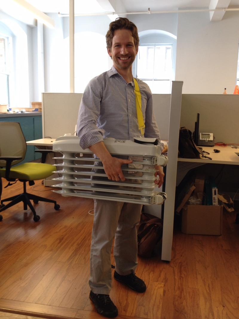 Radiator Labs founder and CEO Marshall Cox with a radiator he uses for demonstrations slung over his shoulder