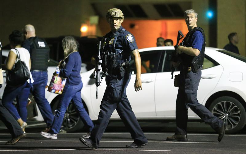 Dallas police officers escort residents near the scene where 11 police officers were shot and five have now died on July 8, 2016 in Dallas, Texas.