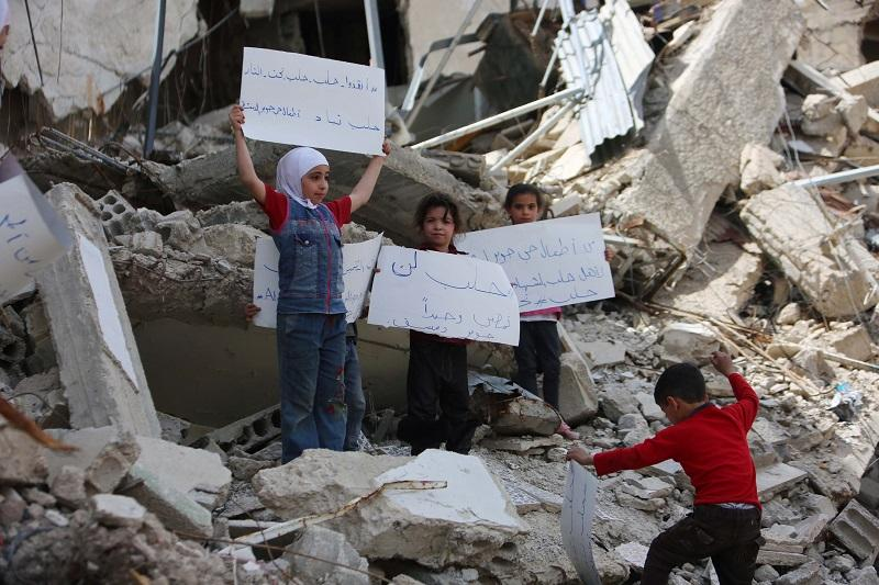 Syrian kids gather around the rubble of houses at Damascus' Cobar region to protest against Assad Regime forces' air attacks targeting Aleppo on April 30, 2016.