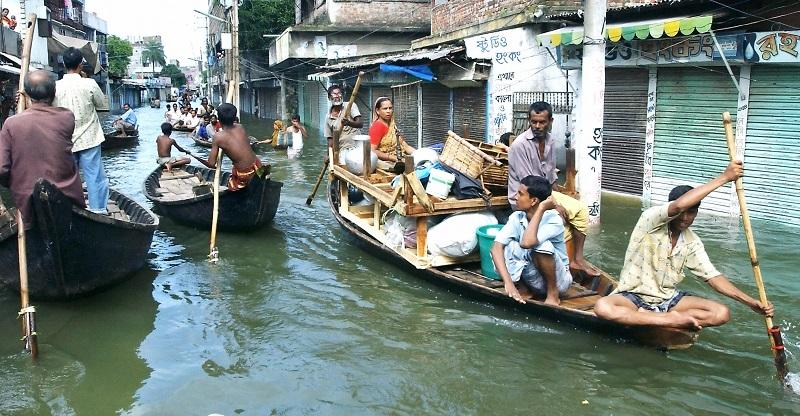 Bangladeshi flood victims use boats laden with their possessions to navigate flooded city streets in Dhaka, 26 July 2004.