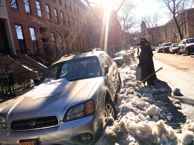 A couple in Brooklyn Heights attempts to dig their car out to make way for snow removal.
